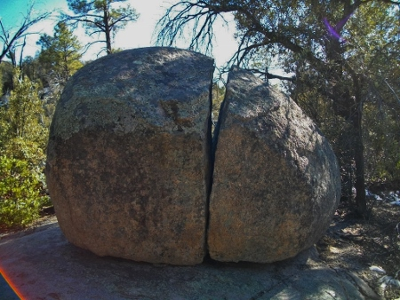 A huge boulder cracked by natural elements.