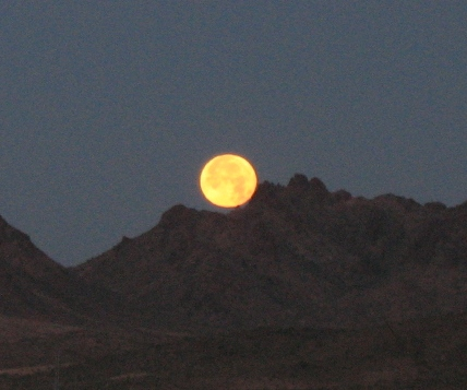The moon setting in the west, behind the mountains flanking the Colorado River on the Yuma Proving Grounds.